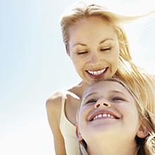 Mamá e hija sonriendo al aire libre